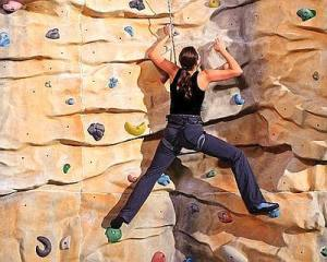 active young woman on rock wall in sport centre